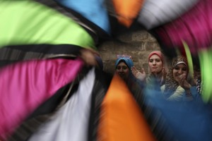 Women watch a whirling dervish perform a traditional dance on the famous Al-Moez Street in Cairo
