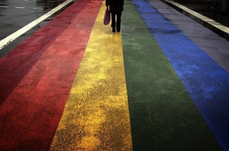 A pedestrian walks across a rainbow pedestrian crossing painted on Sydney's Oxford street, the city's main gay district April 4, 2013. REUTERS/David Gray